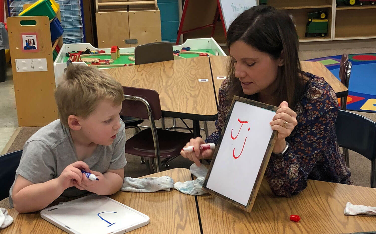 Minnewaska area preschool student practicing writing letters with his teacher